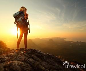 Turysta z plecakiem na szczycie góry o wschodzie słońca