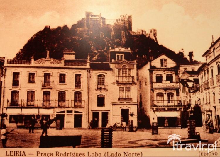 Zabytkowa pocztówka przedstawiająca główny rynek miasta i widok na zamek